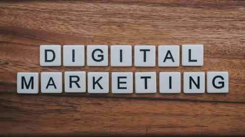 """Digital Marketing"" spelled out using tiles on a wooden surface. Online marketing methods help reach your customers."
