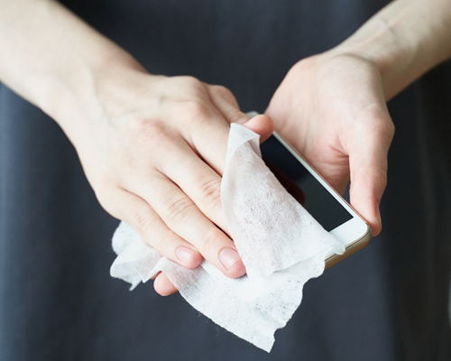 Hands cleaning an iPhone with an alcohol wipe, showing how to properly clean electronics