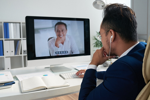 A man video conferences with another man, using the best video conferencing app for them.