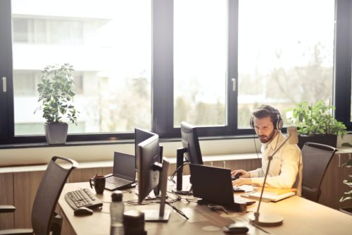 An IT support man sits at his desk on his computer. Outsourcing your IT services provides many benefits.