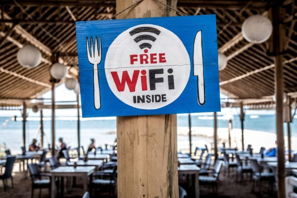 Free Wi-Fi sign outside of restaurant. Learn how to stay safe on public Wi-Fi.